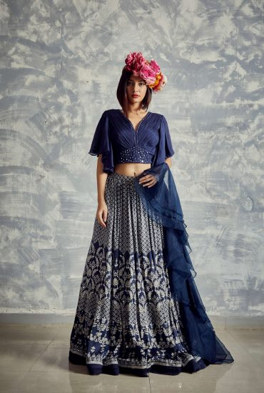 Midnight blue printed lehenga in natural fibre satin weave with chiffon pleated crop top with bell sleeves & mirror work teamed with frivolous organza dupattaMidnight blue printed lehenga in natural fibre satin weave with chiffon pleated crop top with bell sleeves & mirror work teamed with frivolous organza dupatta