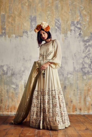 Timeless Crème cut-out long dress in Tussar with beautiful floral printed ghehra & delicate embroidered Jacket teamed with two-tone organza dupatta