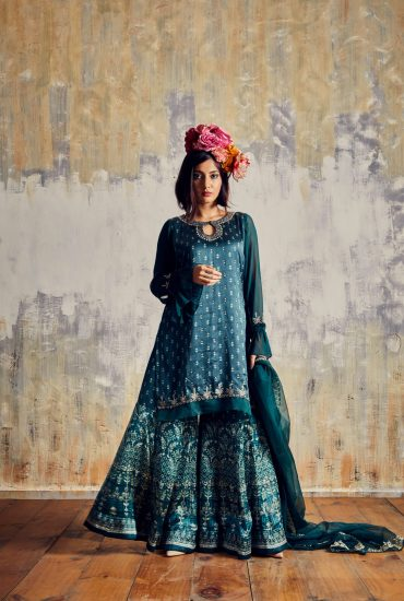 Bottle green Sharara set in satin weave with beautiful Mughal print & intricate handwork on neckline , sleeve & is teamed with organza dupatta